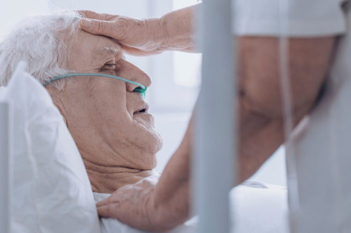 Close-up of a person taking care of sick senior man, touching his forehead