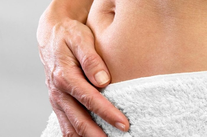 closeup of a person's abdomen wrapped in a towel, hand pressed against the stomach