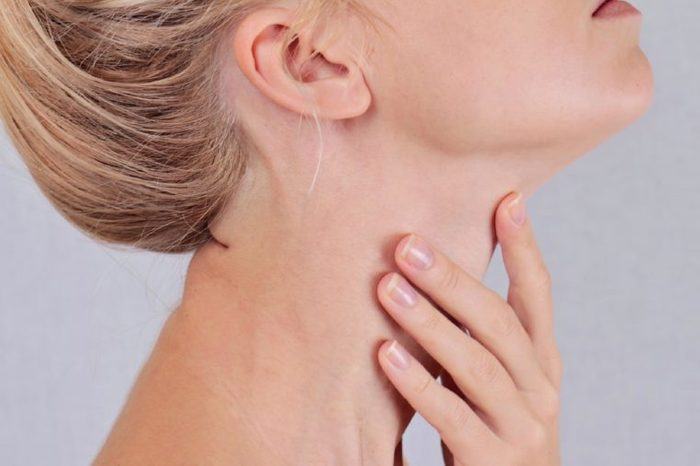 closeup of a woman's neck, head tilted back and hand on throat