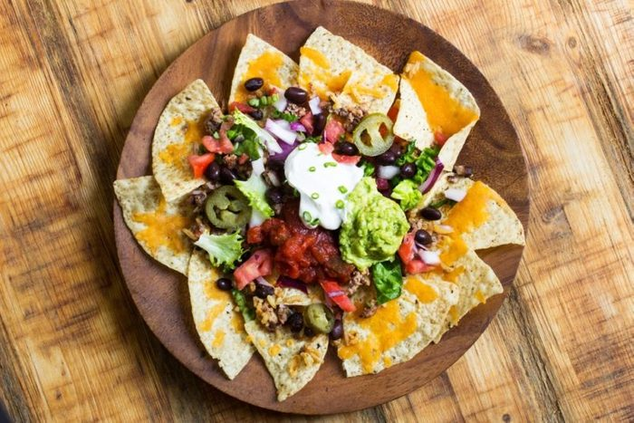 Homemade Nachos with chips salsa guacamole and cheese, overhead view
