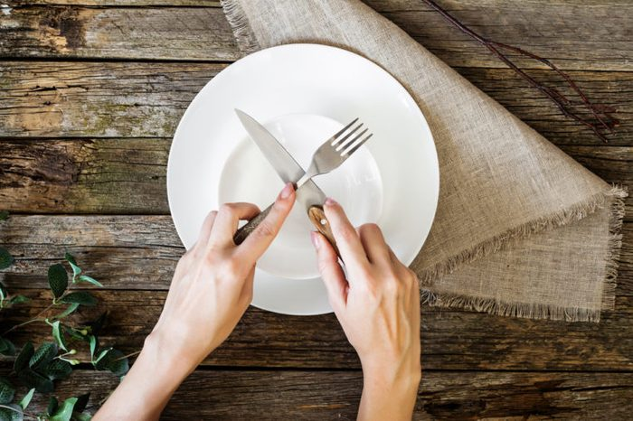 hands holding knife and fork on a plate, top view