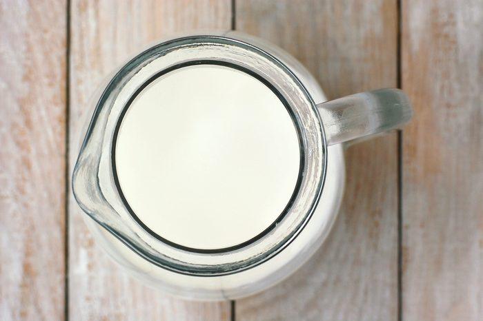 White milk in glass jug on wooden background