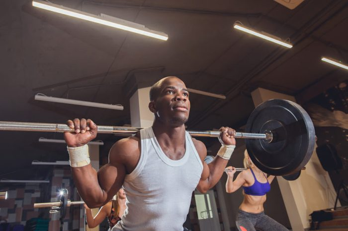Fit young people lifting barbells over their heads looking focused, working out in a gym with other people