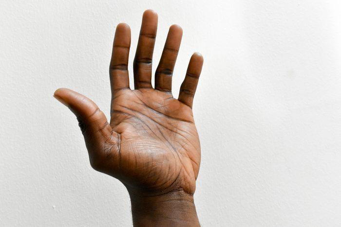 left hand of dark skin man isolated on white background