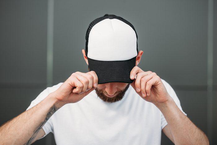 Man wearing black and white baseball hat