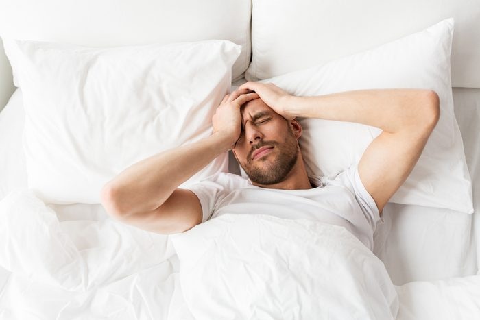 man lying in bed suffering from headache or hangover