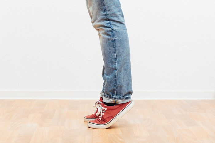 Man on tip toes, anonymous bottom half crop, indoors studio people shot.