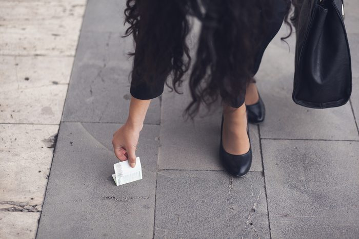 Close-up Of A Woman Picking Up money On Street