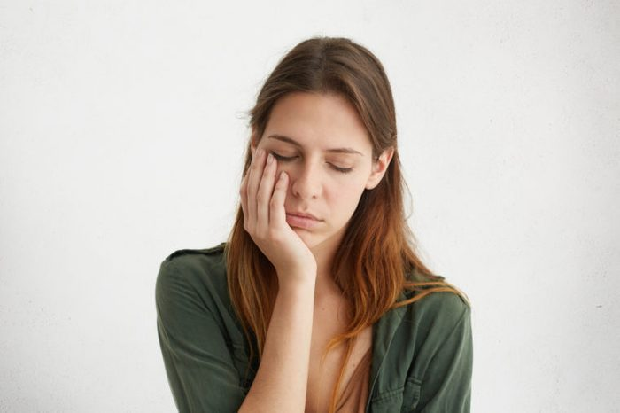 Cute woman looking tired, holding her hand on cheek. closing her eyes with tiredness. Young woman having sad expression and toothache. People, problems, tiredness concept