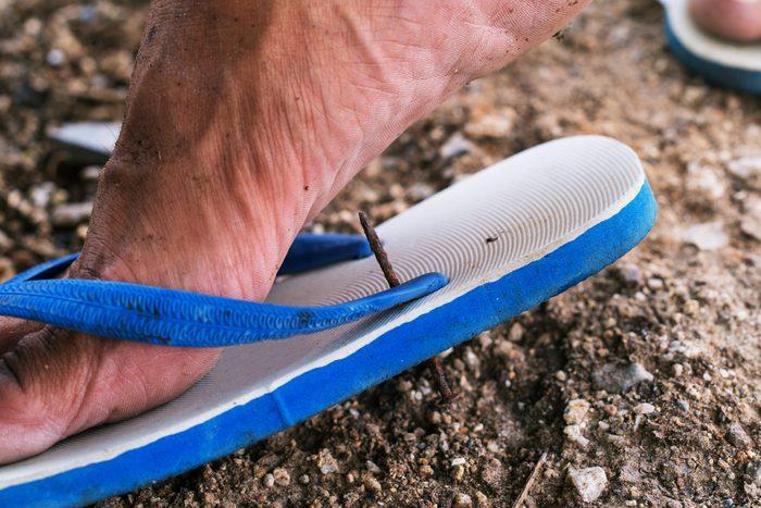close up of nail through flip flop shoe