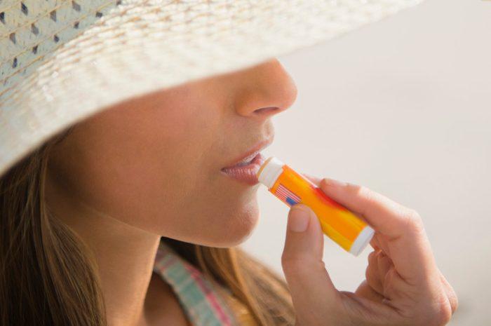 woman applying lip balm sunscreen at the beach