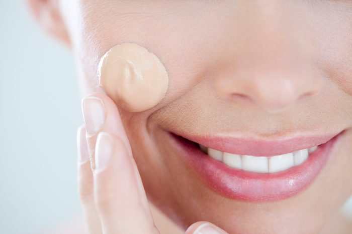 close up of woman applying foundation makeup on face
