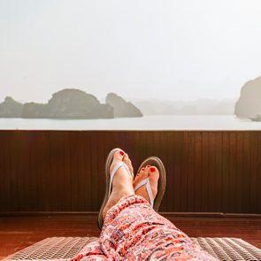 view of woman's legs laying outside wearing flip flops