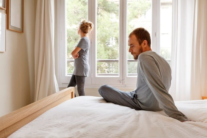 mid adult couple in bedroom having an argument