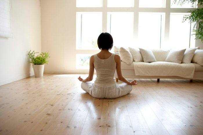 young woman meditating at home