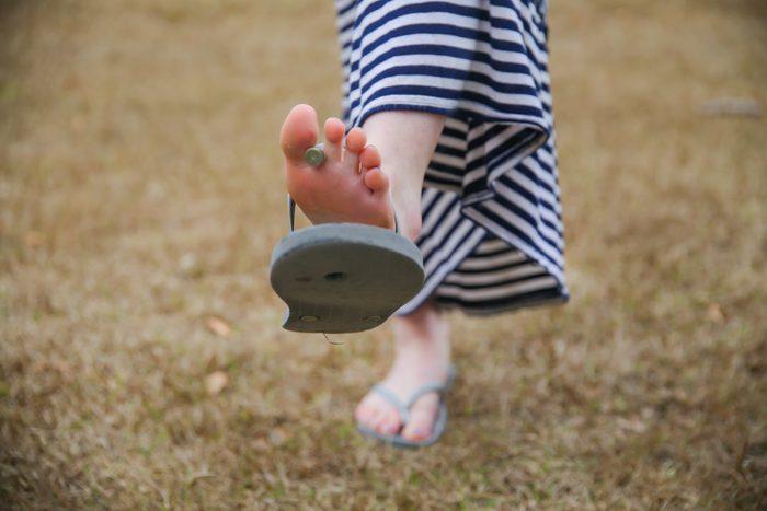 woman wearing broken flip flop