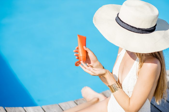 woman in sunhat applying sunscreen by the water