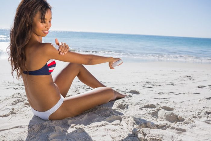 Attractive woman in bikini applying sun cream on her shoulder while sunbathing on the beach