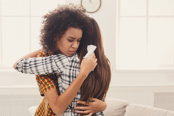 Woman hugging her depressed friend at home, closeup. Young girl supporting her crying girlfriend. Friendship consoling and care, copy space