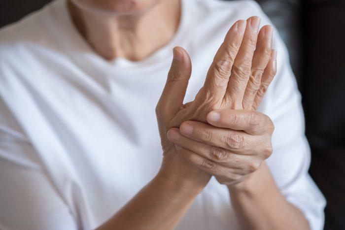 senior woman holding hand with arthritis pain