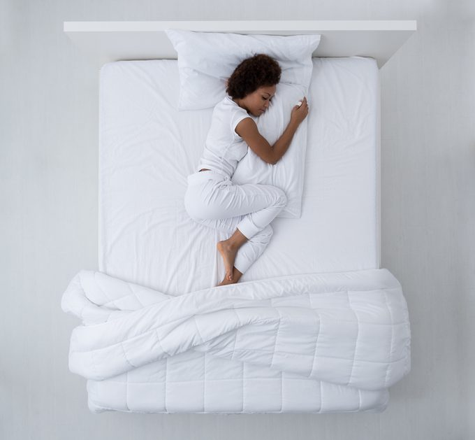 Beautiful african american woman lying in bed and sleeping, top view