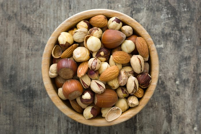 Assorted mixed nuts in bowl on wooden table