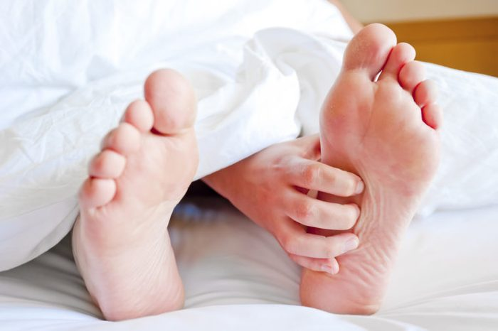 Feet sticking out from under the covers; hand itching foot