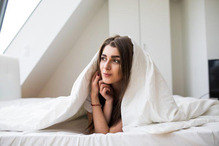 Smiling woman under a duvet in her bedroom
