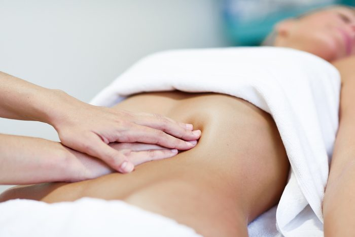 Hands massaging female abdomen.Therapist applying pressure on belly. Woman receiving massage at spa salon