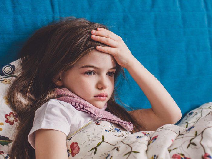 Little girl holding her head in pain