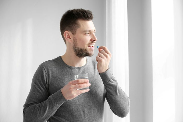 Handsome young man taking pill at home