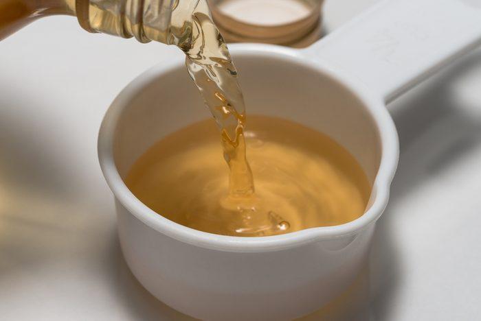 Pouring a quarter cup of apple cider vinegar