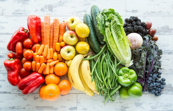 Variety of fresh fruits and vegetables sorted by colors