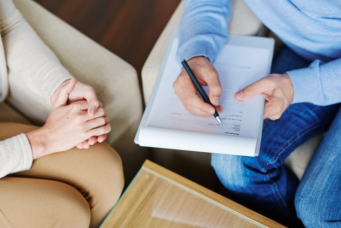 Depressed patient sitting nervously on sofa and explaining her problem to psychologist with clipboard and pen