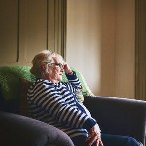 senior woman sitting at home alone