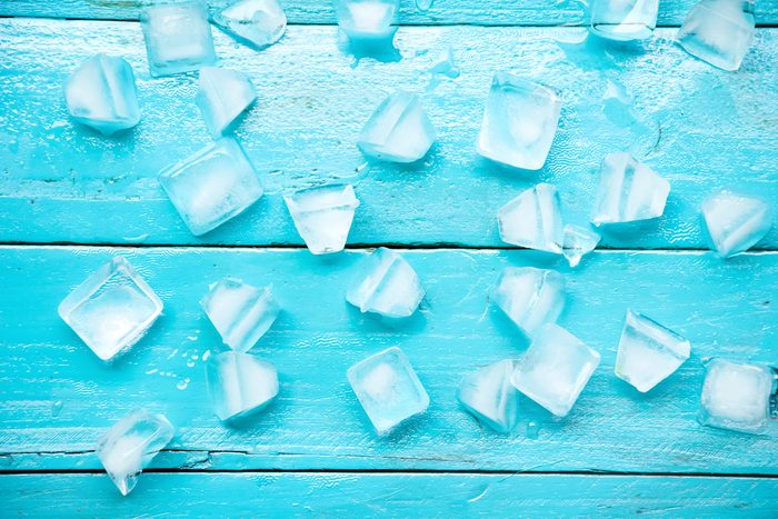 many cold ice cubes on blue wood background
