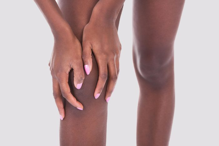 Midsection of African American woman suffering from knee pain against white background