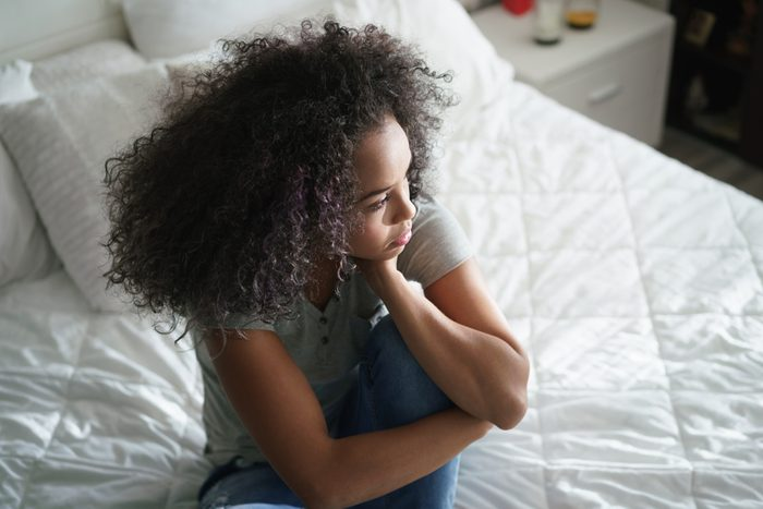 woman sitting on bed, looking sad