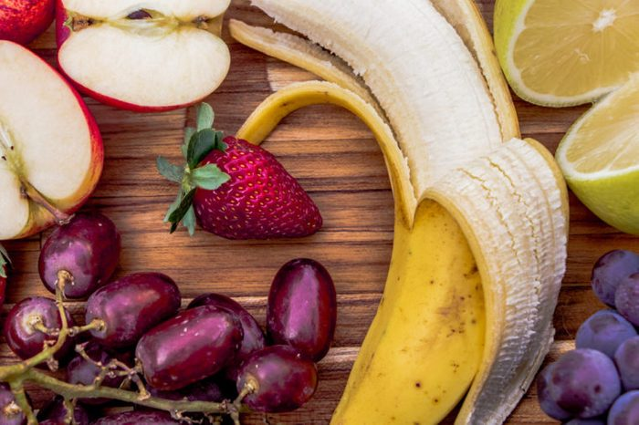 Fresh fruits: banana, grapes, lemon, and apple