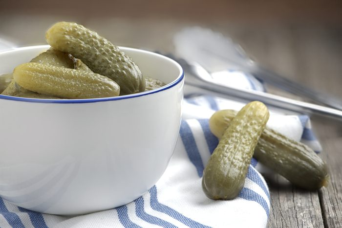 Dill pickles gherkins cucumber in white bowl