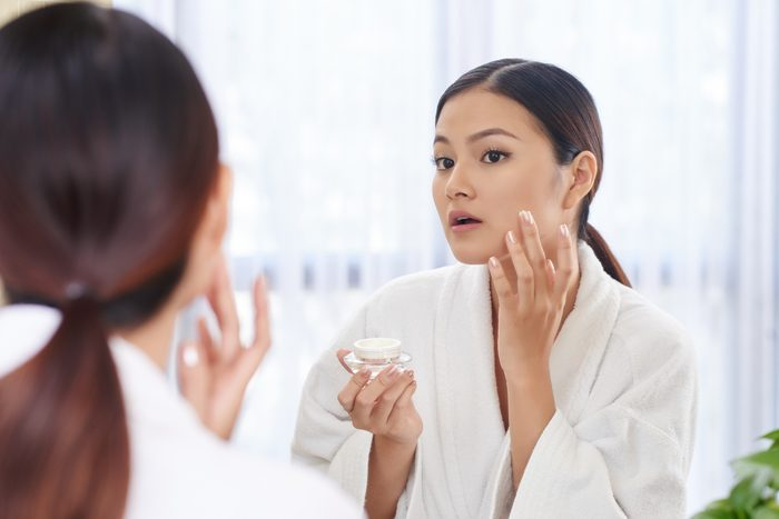 woman applying cream to her face