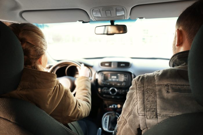 Young woman driving car with man in passenger seat