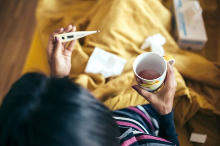 Sick woman drinking tea holding thermometer on couch