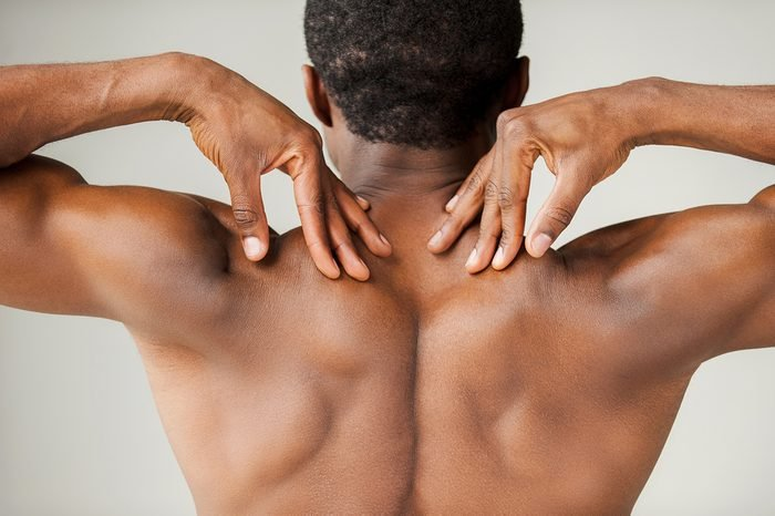 Muscular black man. Rear view of young muscular black man touching his shoulders while standing isolated on grey background