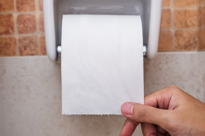 Close-up roll toilet paper in restroom with hand pulling