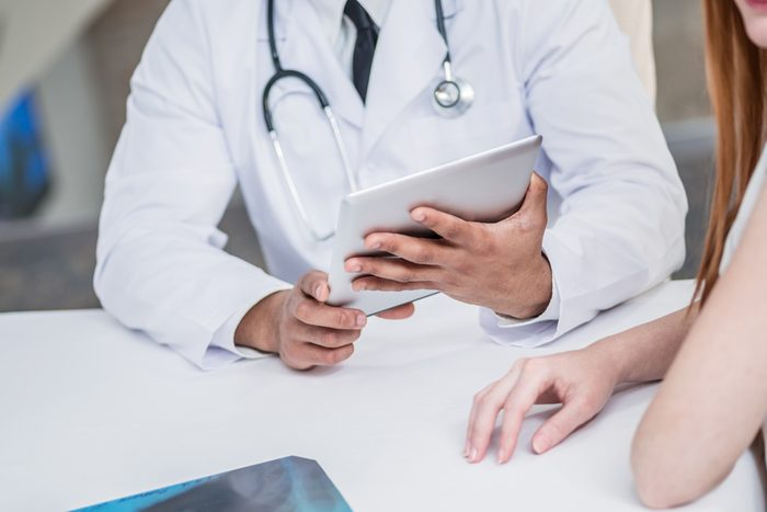 Checking medical tests. Serious doctor and patient. Doctor holding tablet and talking with a patient in the hospital. Close-up view of the hands and the tablet.