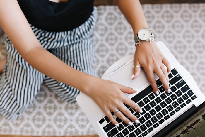 Woman with tanned skin typing on keyboard while standing on her knees. Girl in trendy silver accessories using laptop sitting on carpet with ornament.