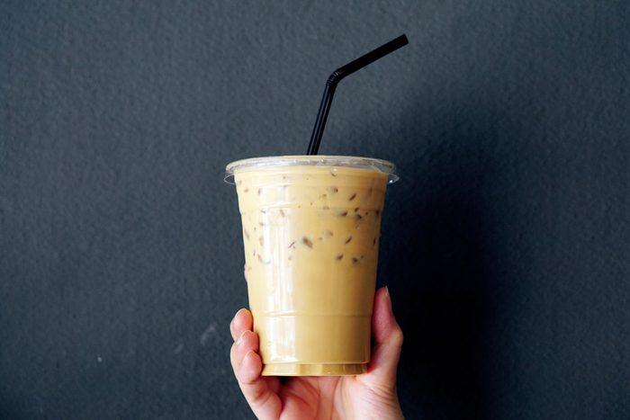 Woman holding plastic glass of iced coffee with milk on grey background