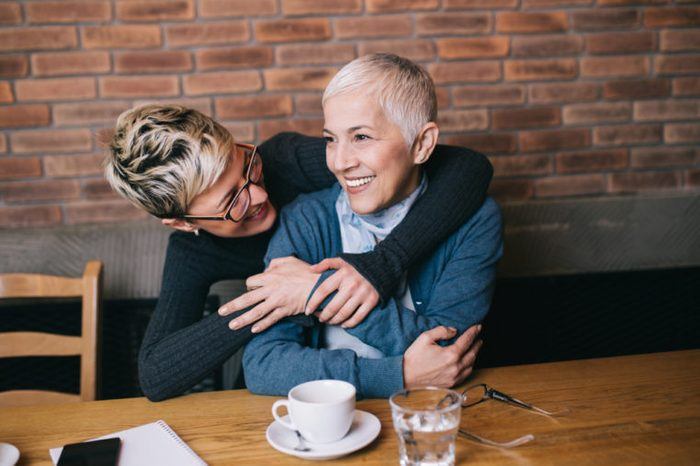 Senior mother sitting in cafe bar or restaurant with her middle aged daughter and enjoying in conversation.