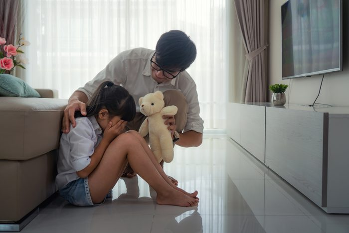 father trying to comfort crying daughter